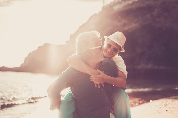 Starszy para korzystających na plaży, starszy mężczyzna niosący żonę na plecach i zabawy podczas letnich wakacji. stara kobieta cieszy się jazdą na barana na plecach męża na plaży