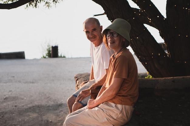 Starszy para łysy mężczyzna i azjatka siedzą w parku i rozmawiają podczas spaceru latem