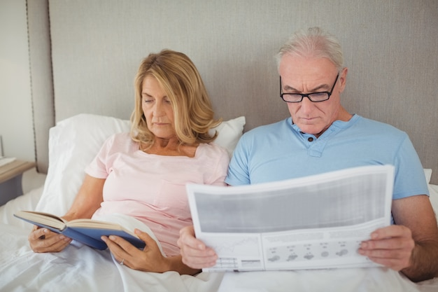 Starszy para na łóżku czytania gazety i książki