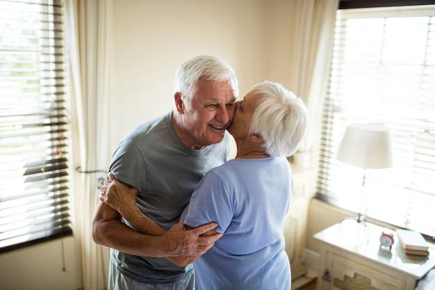 Starszy para obejmując siebie w sypialni w domu