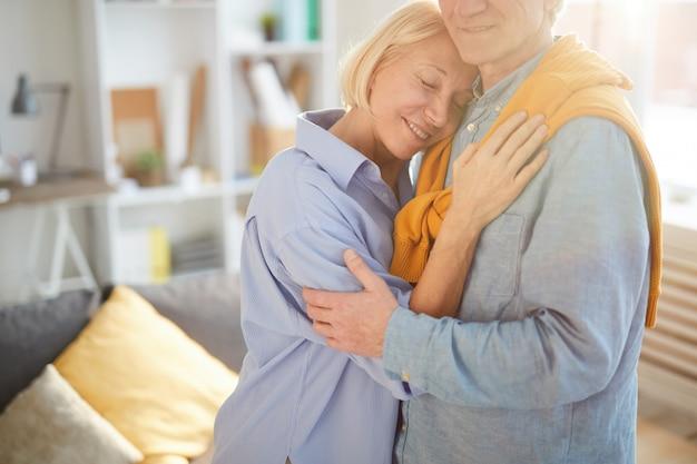 Starszy para obejmując w przytulnym pokoju
