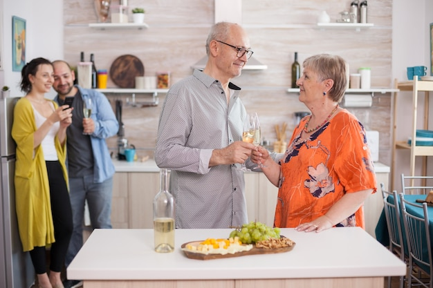 Starszy para patrząc na siebie trzymając kieliszki do wina w kuchni. młody mężczyzna i kobieta robienia zdjęć telefonem podczas spotkania rodzinnego.