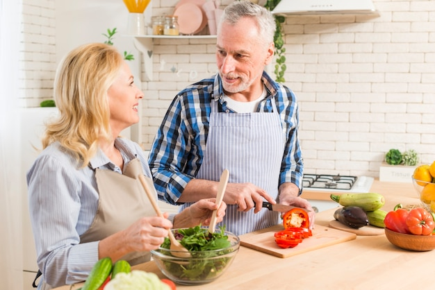 Starszy para przygotowuje sałatkę w nowoczesnej kuchni patrząc na siebie