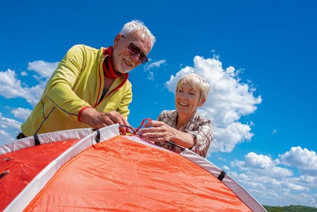 Starszy para przygotowuje się do odpoczynku, rozkładając namiot