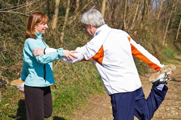Starszy para robi ich ćwiczenia biegowe,