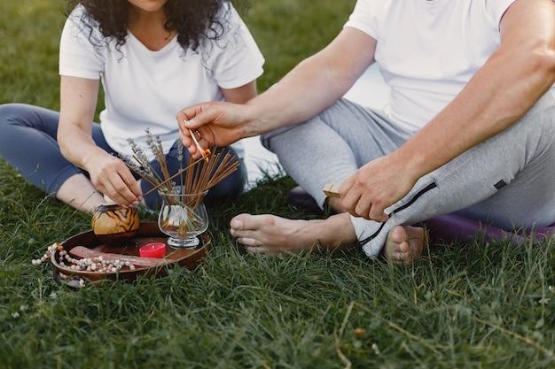 Starszy para robi joga na świeżym powietrzu. rozciąganie w parku podczas wschodu słońca. brunetka w białej koszulce.