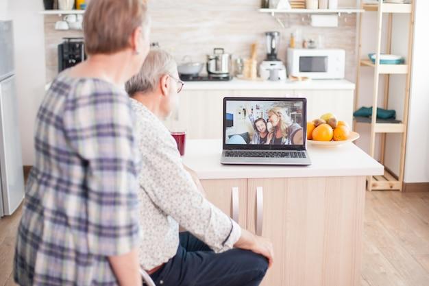 Starszy para rozmawia z siostrzenicą i córką na wideorozmowę online z kuchni. osoby w podeszłym wieku korzystające z nowoczesnej komunikacji online internet web techonolgy.