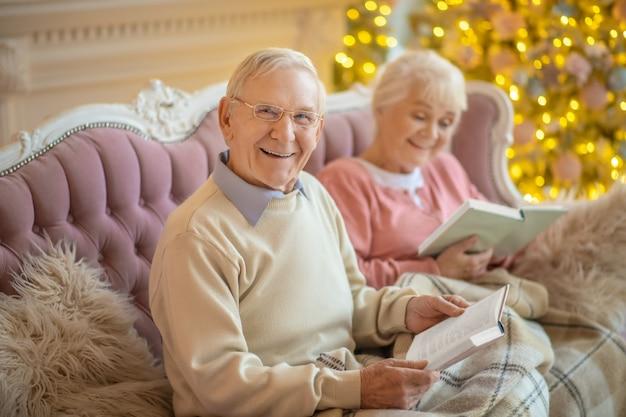 Starszy para siedzi na kanapie i czytając książki