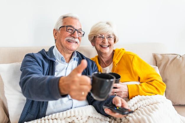 Starszy para siedzi na kanapie, przykryty kocem. czuć się przytulnie, oglądając telewizję. starszy mężczyzna pokazuje kciuk do góry