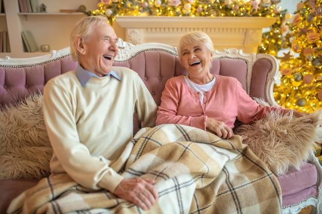 Starszy para siedzi na kanapie razem