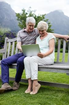 Starszy para siedzi na ławce i za pomocą laptopa