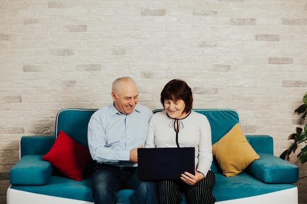 Starszy para siedzi w salonie w domu i nawiązywanie połączenia wideo na laptopie w domu.