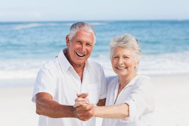 Starszy para tańczy na plaży