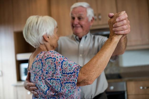 Starszy para tańczy razem w kuchni w domu