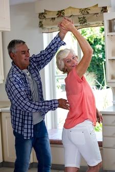 Starszy para taniec w kuchni w domu