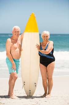 Starszy para trzymając deskę surfingową