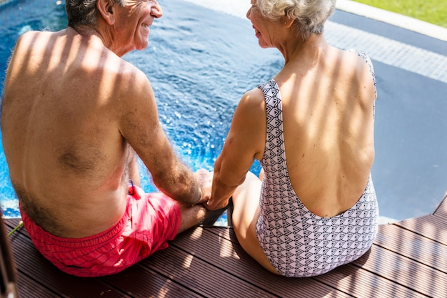 Starszy para trzymając się za ręce przy basenie
