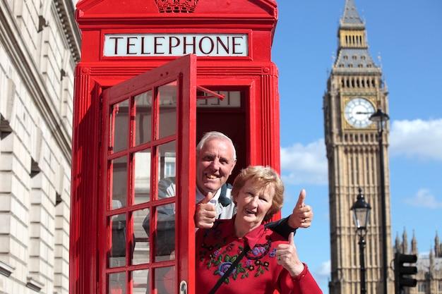 Starszy para w czerwonym polu telefonicznym z big ben w londynie