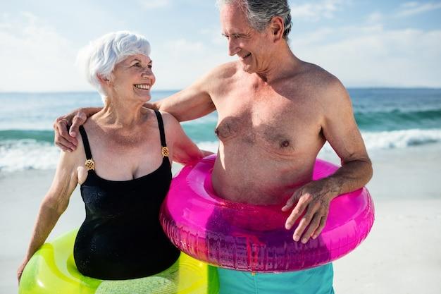 Starszy para w dmuchanym ringu stojąc na plaży