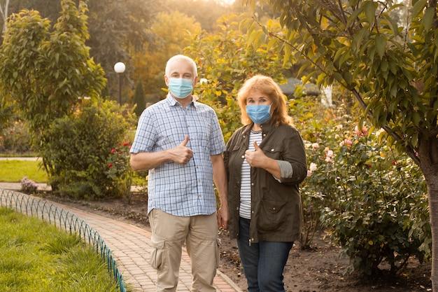 Starszy para w maskach pokazując kciuk do góry