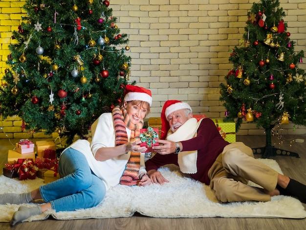 Starszy para z santa claus kapelusz trzymając i patrząc na świąteczny prezent leżąc przed ozdobioną choinką w salonie. kobieta zadowolona z teraźniejszości. romantyczne ferie zimowe.