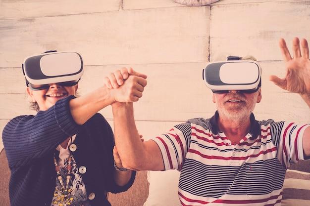 Starszy para zabawy przy użyciu zestawu słuchawkowego vr i obsługi trzymając się za ręce. starsza para korzystających z wirtualnej rzeczywistości. starsza para korzystająca z zestawu słuchawkowego wirtualnej rzeczywistości w domu