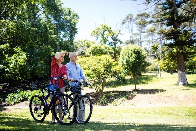 Starszy pary odprowadzenie z bicyklem w parku