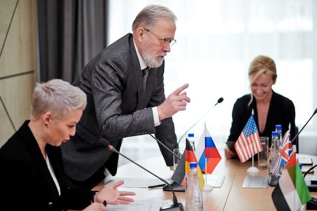 Starszy, pewny siebie mówca w eleganckim szarym garniturze, wyjaśniający swoją opinię partnerom, innym kierownictwu na wieloetnicznym spotkaniu w biurze, używając mikrofonów do wygłaszania przemówień
