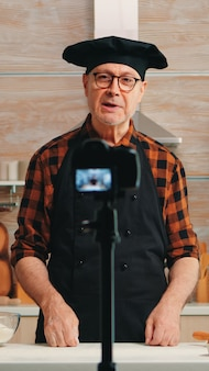 Starszy piekarz nagrywa samouczek wideo o przepisie na jedzenie w kuchni. emerytowany bloger chefinfluencer wykorzystujący technologię internetową do komunikacji, strzelania, blogowania w mediach społecznościowych za pomocą sprzętu cyfrowego
