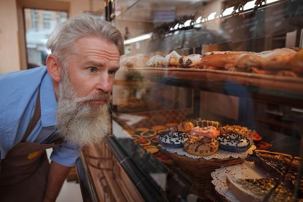 Starszy piekarz oglądający ekspozycję detaliczną w swojej piekarni, patrząc na pyszne pączki