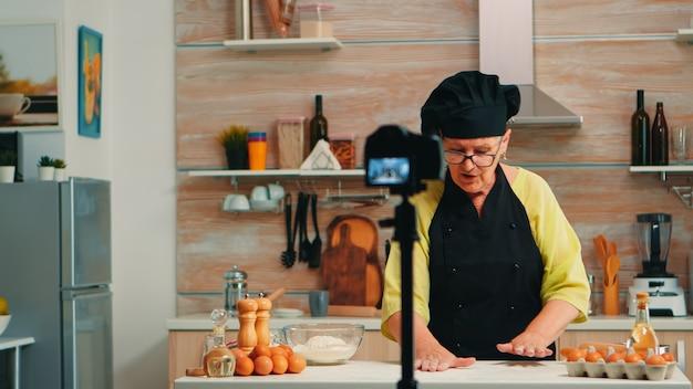 Starszy piekarz opowiada o mące podczas nagrywania samouczka wideo. emerytowany bloger, szef kuchni influencer wykorzystujący technologię internetową, komunikujący się, strzelający, blogujący w mediach społecznościowych za pomocą sprzętu cyfrowego