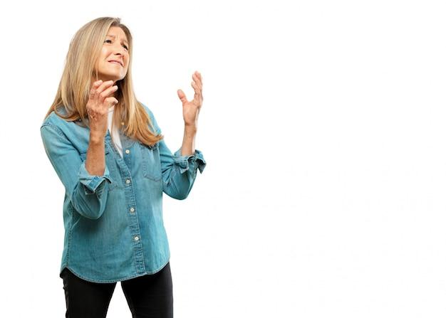 Starszy piękna kobieta szuka zestresowany i sfrustrowany, patrząc w górę i trzymając obie ręce otwarte