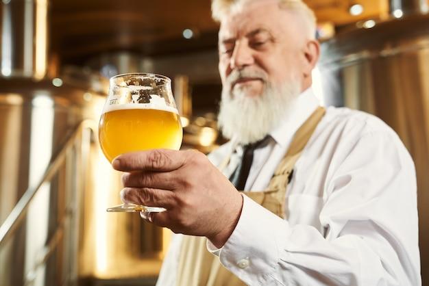 Starszy piwowar trzyma szkło z lekkim piwem