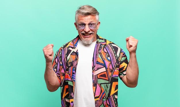 Starszy podróżnik czuje się zszokowany, podekscytowany i szczęśliwy, śmieje się i świętuje sukces, mówiąc wow