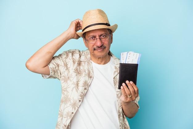 Starszy podróżnik indyjski mężczyzna w średnim wieku posiadający paszport na białym tle na niebieskim tle jest zszokowany, pamięta ważne spotkanie.