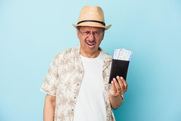 Starszy podróżnik indyjski mężczyzna w średnim wieku posiadający paszport na białym tle na niebieskim tle krzyczy bardzo zły i agresywny.