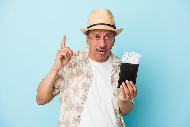 Starszy podróżnik indyjski mężczyzna w średnim wieku posiadający paszport na białym tle na niebieskim tle o pomysł, koncepcja inspiracji.