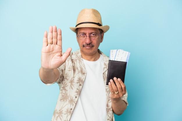 Starszy podróżnik indyjski mężczyzna w średnim wieku posiadający paszport na białym tle na niebieskim tle stojący z wyciągniętą ręką pokazując znak stopu, uniemożliwiając.