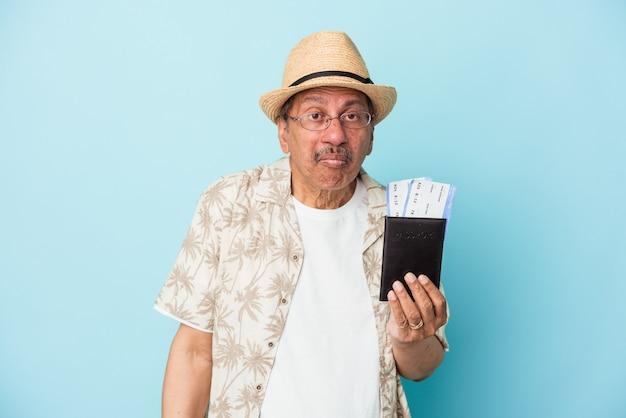 Starszy podróżnik indyjski mężczyzna w średnim wieku posiadający paszport na białym tle na niebieskim tle wzrusza ramionami i otwiera oczy zdezorientowany.