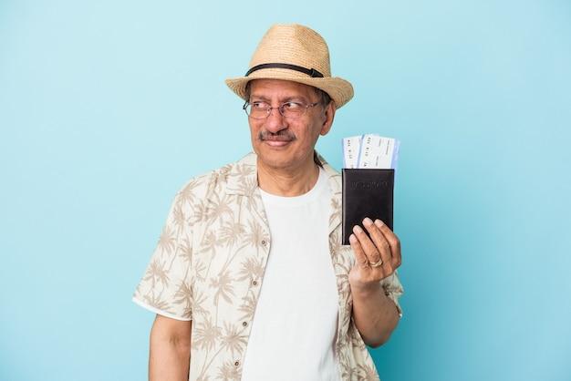 Starszy podróżnik indyjski mężczyzna w średnim wieku posiadający paszport na białym tle na niebieskim tle zdezorientowany, czuje się wątpliwy i niepewny.
