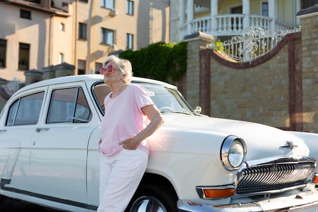 Starszy podróżnik stojący w gnieździe przy swoim samochodzie