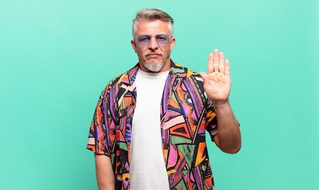 Starszy podróżnik turysta wyglądający poważnie, niezadowolony i zły, pokazujący otwartą dłoń wykonujący gest stopu