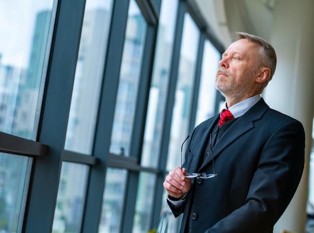 Starszy poważny biznesmen stojący w pobliżu okna z panoramicznym widokiem na miasto. człowiek myśli podczas sprawdzania wiadomości e-mail, stojąc w pobliżu okna. zdjęcie z boku.