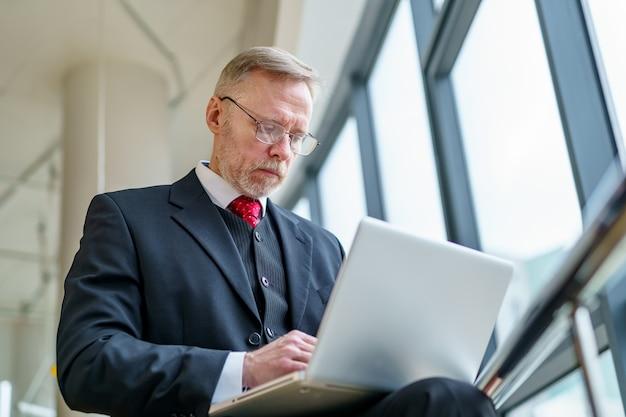 Starszy poważny biznesmen stojący w pobliżu okna z panoramicznym widokiem na miasto. laptop w rękach, człowiek myślący podczas sprawdzania wiadomości e-mail, stojący w pobliżu okna.