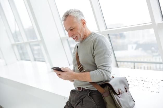 Starszy pozytywny optymistyczny siwowłosy biznesmen brodaty w pomieszczeniu na czacie przez telefon komórkowy.