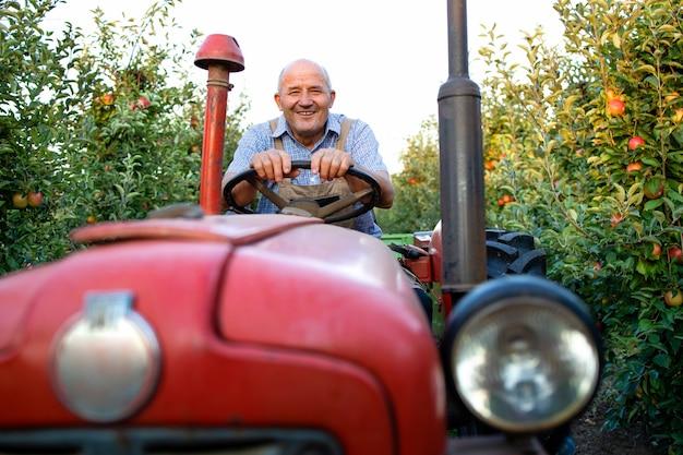 Starszy pracownik prowadzący swoją starą maszynę ciągnikową w stylu retro przez sad jabłoniowy
