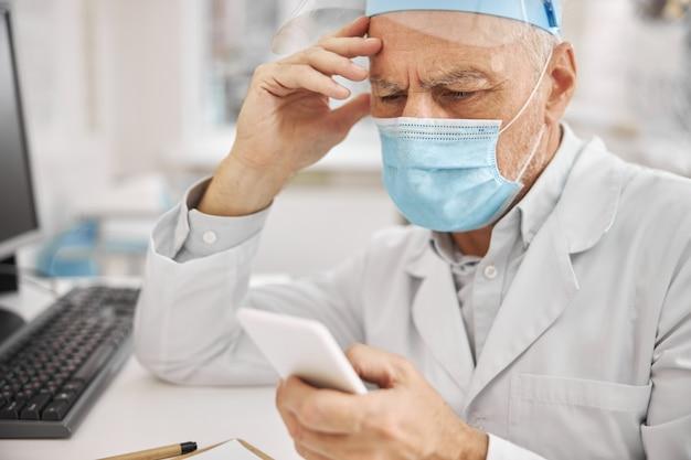 Starszy pracownik służby zdrowia noszący maskę ochronną i wyglądający na zamyślonego podczas sprawdzania telefonu