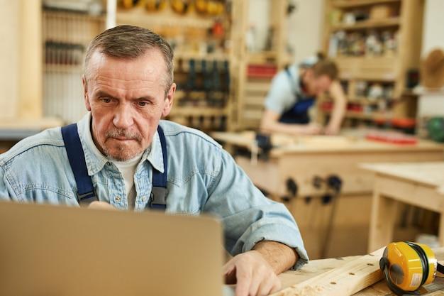 Starszy pracownik używa laptop