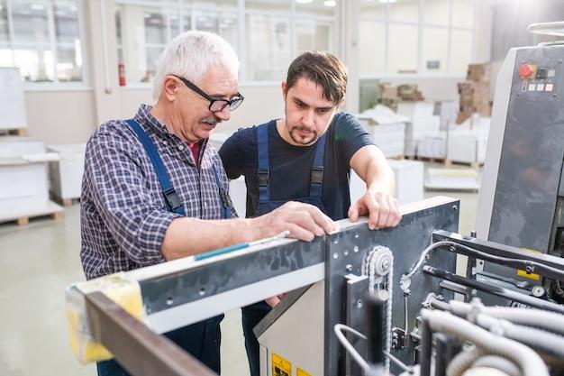 Starszy pracownik w okularach wyjaśniający młodemu koledze z nowoczesnej fabryki ustawienia maszyny drukarskiej