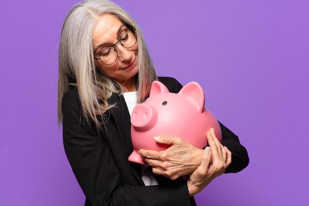 Starszy pretty bizneswoman z piggy bank